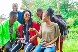 group of young african friends hanging out together outdoors on a bench and laughing as they discuss