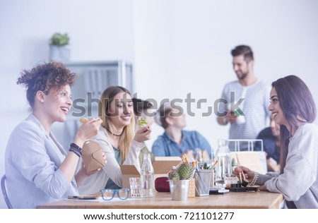 Group of young ambitious workers eating their lunch at the office