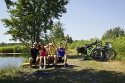 Group of young and attractive people sitting on a log in front of the camera next to the river and bicycles. Happy backpackers touring around the Baltic sea.