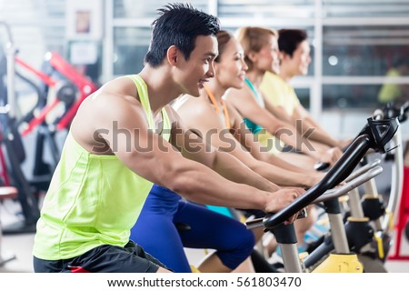 Group of young Asian athletes side by side during spinning class workout