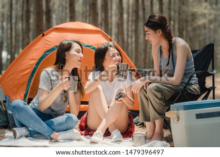 Group of young Asian friends camping or picnic together in forest, teenager female enjoy moment talking in front of their tent. Women do adventure activity and travel on holidays vacation in summer. #1479396497