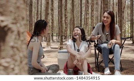 Group of young Asian friends camping or picnic together in forest, teenager female enjoy moment talking in front of their tent. Women do adventure activity and travel on holidays vacation in summer. #1484354915