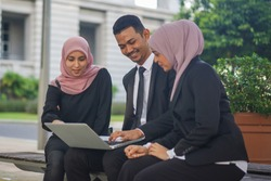 Group of young Asian Muslim corporate having a discussion at the park with notebook