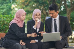 Group of young Asian Muslim corporate makin an online reservation for business trip
