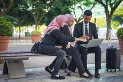 Group of young Asian Muslim corporate making an online reservation for business trip