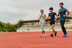 group of young Asian people, fellow students, running or exercising outdoors on the stadium,Asia. Team athletes practice on running track in University Stadium. warm up,mini marathon, Olympic Games