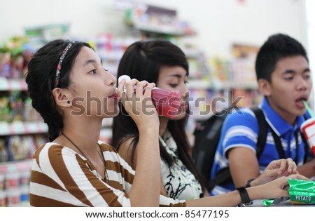 Group of young asian students eating snacks in a restaurant.