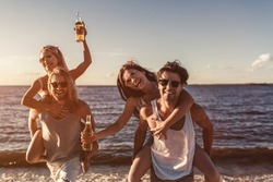 Group of young attractive friends are having fun on beach, drinking beer and smiling.
