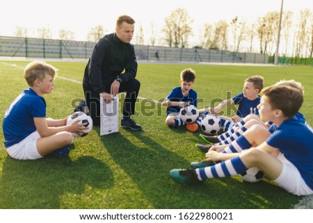 Group of Young Boys Sitting on Sports Grass Field witch School Coach. Kids Listening Coach's Tactic Talk. Young Coach Explain Football Tactic. Coaching Youths in Sports