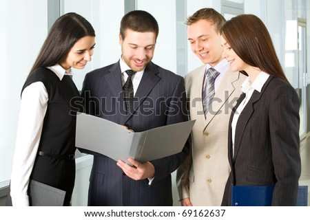 Group of young business people discuss the document in an office corridor