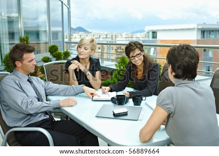 Group of young business people sitting around table on for The terrace group