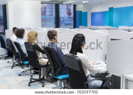 group of young business people with headset working and giving support to customers in a call center office #703597705
