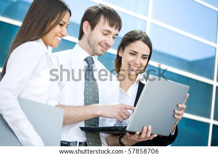 Group of young business people work with the laptop against modern office building