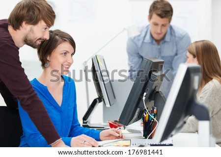 Group of young business people working in the office with focus to a young man and woman sharing a desktop monitor as they check information online against their paperwork