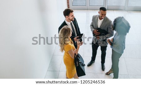 Group of young business professionals standing together and having casual discussing in office hallway. Business colleagues having casual meeting in office lobby.