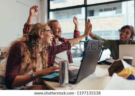 Group of young business team giving high five and celebrating success at office. Cheerful startup business team rejoicing success at office.