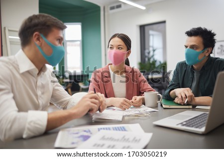 Group of young business team wearing protective masks and discussing work together at the table during meeting