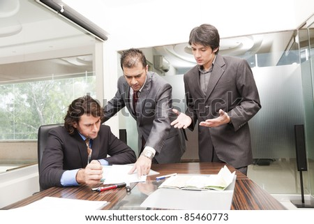 group of young businessmen having a serious and intense discussion in the business meeting.