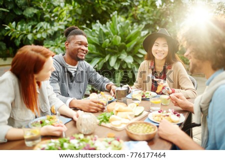 Group of young cheerful friends gathered by dinner table having talk ahile eating homemade food