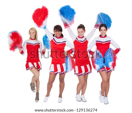 Group of young cheerleaders in red uniform. Isolated on white background