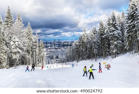 Group of young children learning to practice skiing on a ski slope in Poiana Brasov resort, in winter season, in Romania