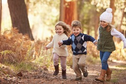 Group Of Young Children Running Along Path In Autumn Forest