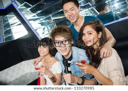 Group of young clubbers drinking cocktails and having fun