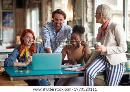 Group of young colleagues are enjoying work with their elderly female boss in a pleasant atmosphere at office. Employees, office, work