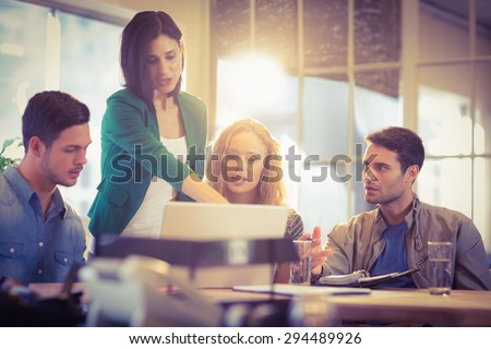 Group of young colleagues using laptop at office