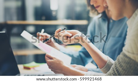 Group of young coworkers working together in modern office.Woman talking with colleague about new startup project.Business people brainstorming concept.Selective focus.Horizontal,blurred