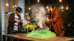 Group of Young Developers Look at Dinosaur and Volcano Eruption in Augmented Reality Through Smartphone. They're Working on the New Virtual Reality Game or Studying History and Geology.