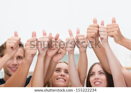 Group of young diverse business people giving a thumbs up standing with their arms raised in the air to indicate their success and approval