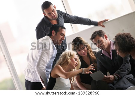 Group of young diverse ethnicity people getting together after a party looking at pictures on a  touch pad