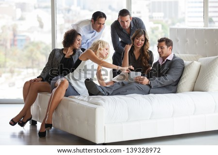 Group of young diverse ethnicity people getting together after work before a party sharing ideas on a mini touch pad