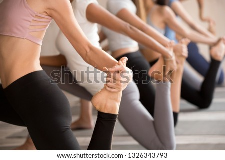Group of young diverse sporty people doing yoga Horse rider exercise, anjaneyasana pose, working out, indoor close up, active female students training at club or studio. Well being, wellness concept Stock fotó ©