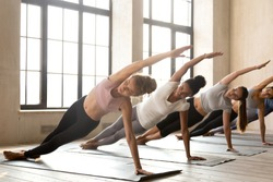 Group of young diverse sporty people doing yoga Vasisthasana exercise, Side Plank pose, working, indoor full length, mixed race female students training at club or studio. Well being, wellness concept