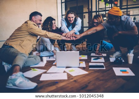 Group of young employees using teambuilding concept feeling unity for reaching success, happy male and female team members celebrating achievement making startup together using laptop computer