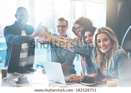 Group of young entrepreneurs in cafe giving each other high five for celebrating success or starting new project, posing and looking at camera #582528751