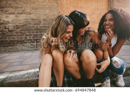 Group of young female friends hanging out in the city. Multiracial young women sitting by the street and having fun. #694847848