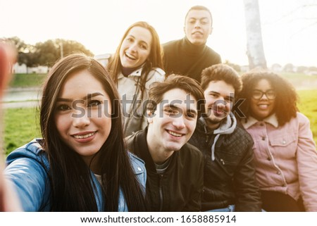 Group of young friends at the park at sunset taking a selfie on a bench with the smart phone - Six people have fun together Foto stock ©