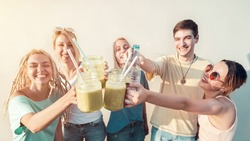 Group of young friends celebratory toast with fresh organic smoothie drinks, healthy drinks and summer concept