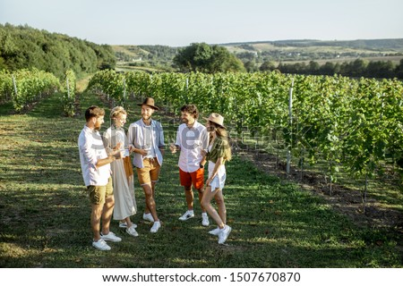 Group of young friends dressed casually hanging out together, tasting wine on the vineyard on a sunny summer morning, beautiful landscape view