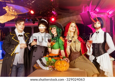 Group of young friends dressed in Halloween costumes are posing at club party