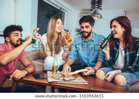 Group of young friends eating pizza and watching tv.Home party.Fast food concept. #1103963615