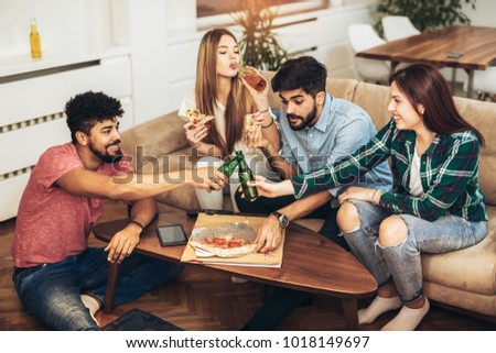 Group of young friends eating pizza.Home party.Fast food concept. #1018149697