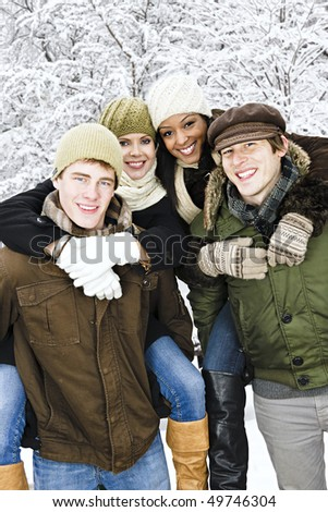 Group of young friends giving piggy back rides outdoors in winter