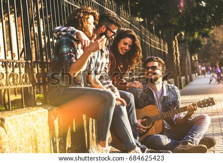 Group of young friends hangout at the city downtown.They singing and playing guitar.