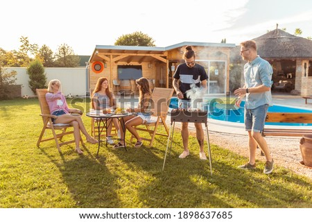 Group of young friends having a backyard barbecue party, grilling meat and having fun while spending sunny summer day outdoor by the swimming pool