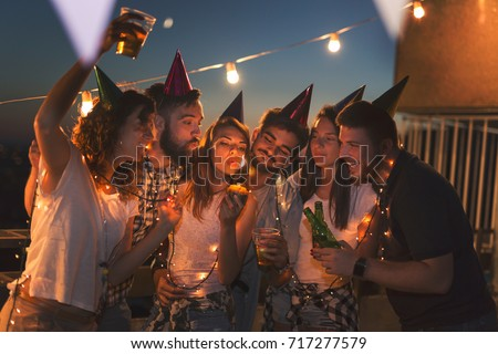 Group of young friends having a birthday party at a building rooftop, singing a song and blowing a candle. Focus on the people in the middle