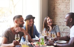 Group of young friends having fun and laughing while dining at table in restaurant.